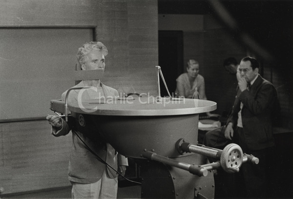 Chaplin, out of costume, rehearses the famous feeding machine sequence
