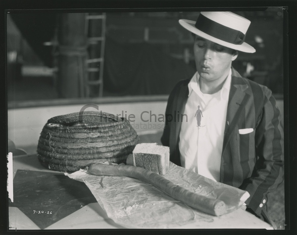 Chaplin enjoying a snake sandwich on the set of The Circus