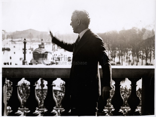Chaplin waves from the balcony of the Crillon Hotel in Paris, 1931