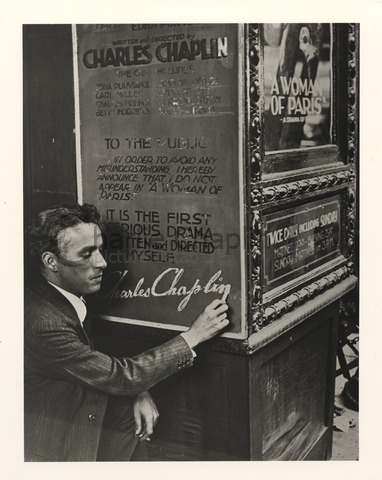 "Chaplin posing next to a poster for A Woman of Paris that reads ""To the public - In order to avoid any misunderstanding, I hereby announce that I do not appear in 'A Woman of Paris'. It is the first serious drama written and directed by myself. Charles Chaplin"""